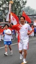 图文-奥运圣火在北京传递 徐祖根手持火炬传递