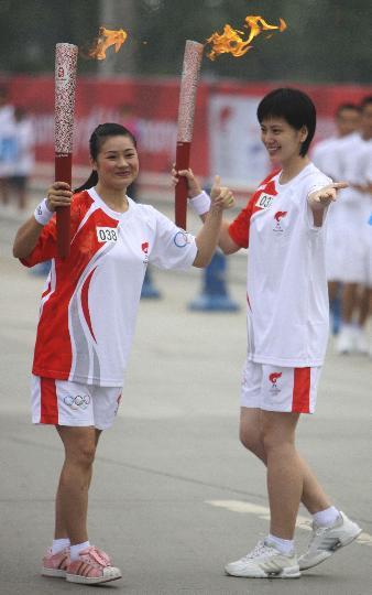 图文-奥运圣火在四川成都传递 沈冰和杨韬交接