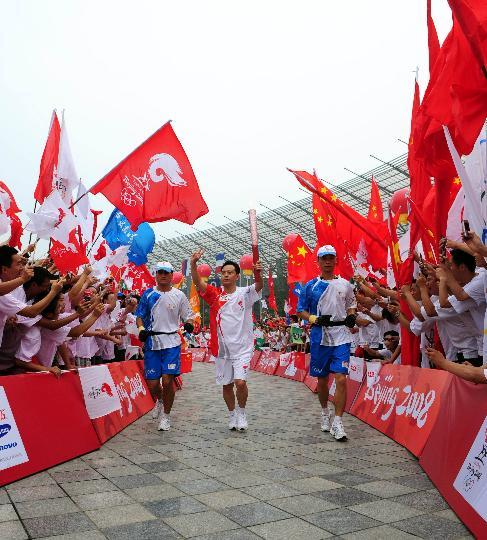 图文-奥运圣火在四川成都传递 余志荣手持火炬传递