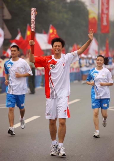 图文-奥运圣火最后一日传递 杨阳手持火炬传递