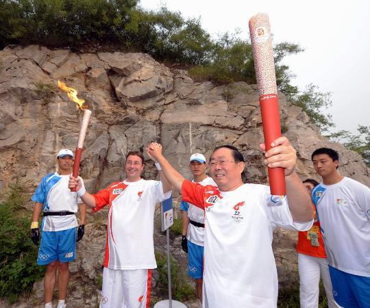 图文-奥运圣火最后一日传递 田雄与施泰纳交接火炬