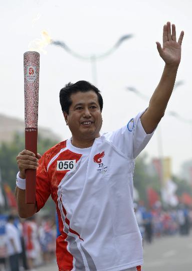 图文-奥运圣火最后一日传递 岑传理手持火炬传递