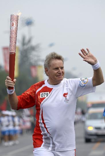 图文-奥运圣火最后一日传递 丹尼斯手持火炬传递