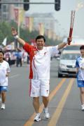 图文-奥运圣火最后一日传递 张春江手持火炬传递