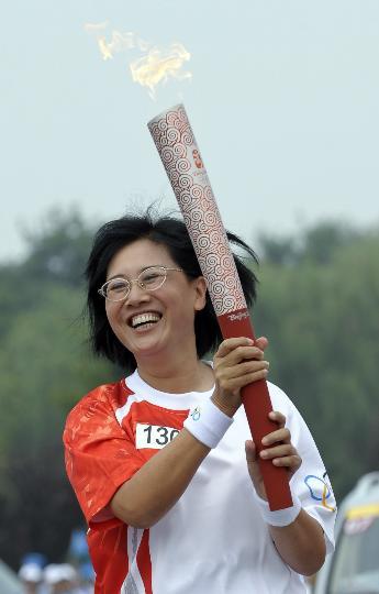 图文-奥运圣火最后一日传递 张明手持火炬传递