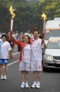 图文-奥运圣火在北京进行首日传递 交接不忘留念