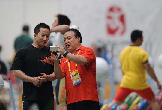 图文-中国举重队首次亮相训练场 石智勇与教练交流