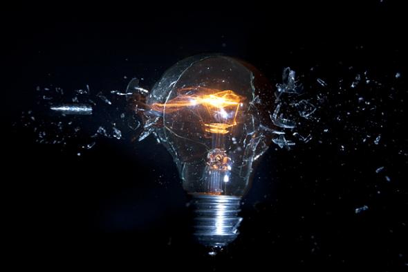 子弹穿过一个亮着的灯泡,灯泡碎了但仍亮着。