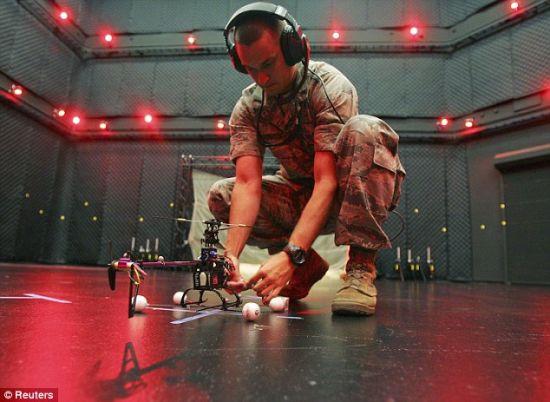 """中尉桑德贝克调整电脑控制的无人机,为在赖特-帕特森空军基地的""""微型鸟舍""""实验室进行的试飞做准备"""