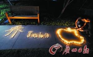 在蘋果總部,有中國留學生通過中文、英文與蘋果標誌組成的蠟光悼念喬布斯。