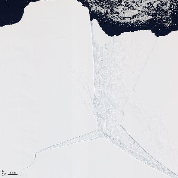照片呈现了艾默里冰架的一小部分,其中有三条巨大的裂缝交汇。最大的那条裂缝与冰流的方向相同,并且逐渐变宽(照片中央)。