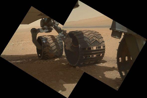 """美国宇航局11日公布了这张""""好奇""""号的轮子在火星表面前进的新图片,该图是利用高清火星相机拍摄的,当时它的防尘罩第一次打开"""