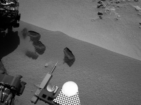 """美国宇航局""""好奇""""号火星车收集样本时在火星表面留下的3个小坑。照片由""""好奇""""号右侧的导航相机在10月15日(""""好奇""""号任务的第69个火星日)拍摄,机械臂清晰可见"""