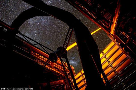 智利欧洲南方天文台帕拉纳尔天文台操作的这个新PARLA激光器。从图上可以看到,7瓦特激光器发出的橙黄色光束从甚大望远镜的望远镜4的穹隆结构射向高空。在背景图上还能看到大麦哲伦云
