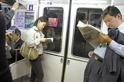 日本地铁上的阅读者。