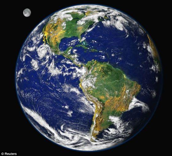 """这是由""""阿波罗""""号的宇航员拍摄的具有标志性的著名""""蓝色弹珠""""图片的升级版。这张数字图像是用几颗卫星1997年从肉眼大约可见的地球轨道里收集的数据合成的,通过附加的艺术授权,月球成为它的背景画面"""