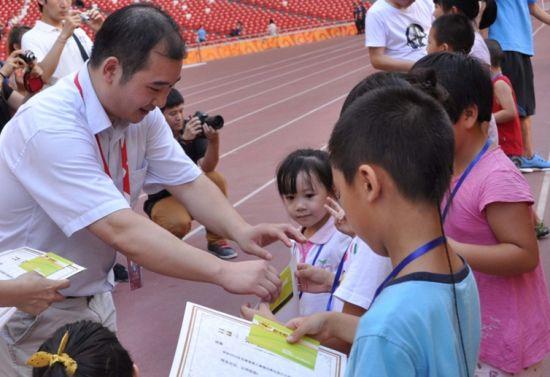 图为:颁奖嘉宾国家体育场有限责任公司副总经理杨城为小火炬手颁奖