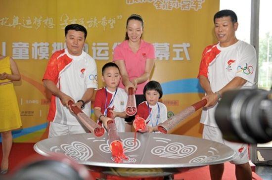 图为:奥运冠军、08年北京奥运会火炬手与鸟巢小火炬手共同点燃鸟巢儿童模拟奥运会主火炬