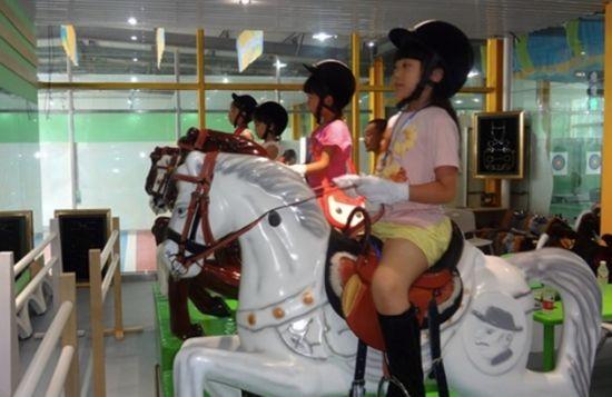 图为:首批奥运小公民在马术赛场体验学习