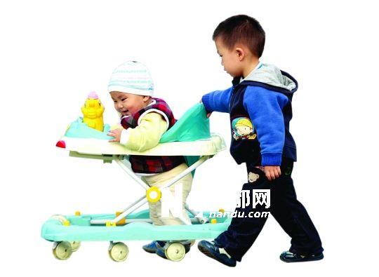 小哥推着小弟的学步车。专家称,小孩过早使用学步车未必是好事,会影响步态。