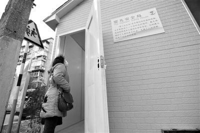 """2013年12月10日,南京首个""""弃婴岛""""安装完毕后,一位市民正在查看内部设施。图/CFP"""