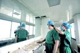 进入手术室前,助手帮他带紧口罩