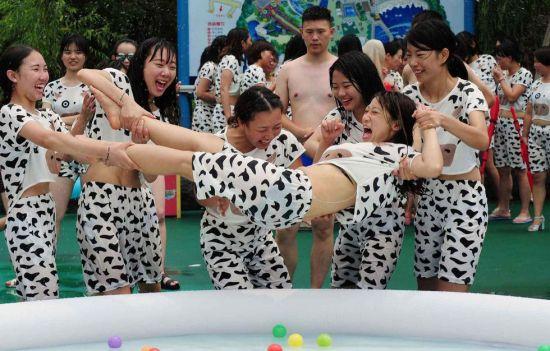 """百名辣妈身着性感的奶牛比基尼,在杭州一公园大玩泼奶狂欢,呼吁全社会都来关注和支持""""母乳喂养""""的观念。(连国庆摄/光明图片)"""