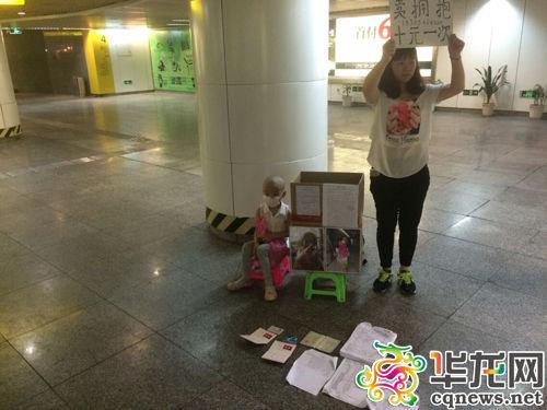 今日下午,重庆两路口轻轨站,陈得娟举着牌子,女儿则坐在她的身边。 实习记者 艾俊锋 摄