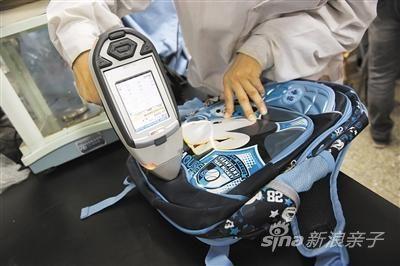 实验人员正在测试书包的重金属含量。两款书包测出重金属铅。