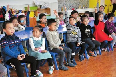 幼儿园里的小朋友举手表达看法 新文化记者 郭亮 摄