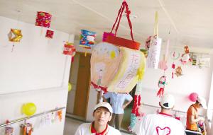 为一名志愿者仰头看悬挂在天花板上的美丽灯笼