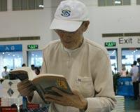 一位老人在翻阅展出图书