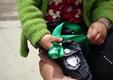 孩子手里紧握的绿丝带