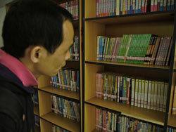 志愿者老肖在查看图书馆藏书