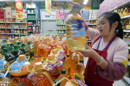 资料图片:10月19日,南京一家超市的工作人员在摆放食用油产品.图片