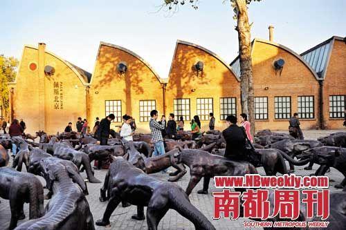2010年11月,在北京798艺术空间的狼群雕塑中游玩的年轻人。