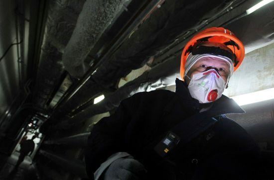 图为一位访客穿过核电站四区的走廊,他身上还佩戴着测量射线强度的仪器