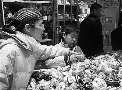 在北京王府井大街一家专营旅游纪念品的店里,顾客正在挑选10元一个的景泰蓝小首饰盒。本报记者陈莹莹摄