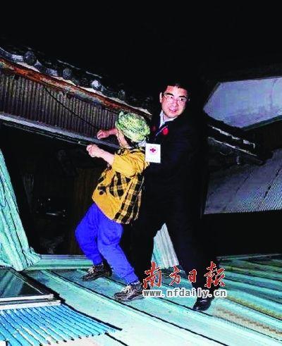 质疑照片二:3月中旬,陈光标在日本地震灾区救援中,将一名日本妇人从危房中救出来,遭网友批驳,称其生硬作秀。资料图片