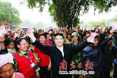 质疑照片三:3月16日,陈光标在云南盈江地震灾区行善时,他让受灾群众一起手举200元捐款合影的行为,再惹争议。CFP供图