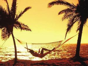 躺在沙滩的吊床上,享受夕阳下宁静的海滩