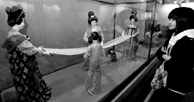 北京非物质文化遗产项目首次大规模在台湾进行展览展示,台北市民在参观北京绢人《捣练图――熨烫卷》。 本版图片新华社发