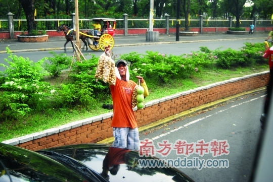 日落大道上,为了生计面带笑容、兜售水果的小贩。