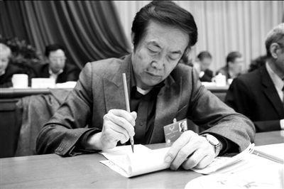 微博政协会议现场,袁熙坤用毛笔做笔记。中新社发