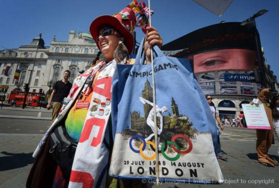 从美国加利福尼亚来到伦敦看奥运的旅行者 Vivianne Robinson在皮卡迪利广场展示她五次奥运会观赛纪念品。(图片来源:美联社)