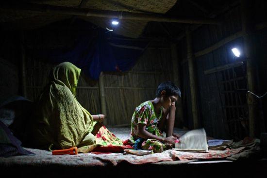 在不通电的孟加拉Natore,一个女孩夜晚利用可充电太阳能灯学习。(图片来源: G.M.B. Akash/PANOS)