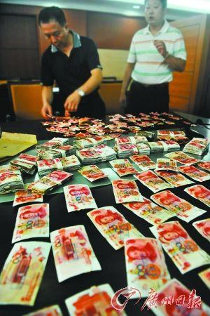 银行工作人员鉴别真假钞后,按规定兑换。