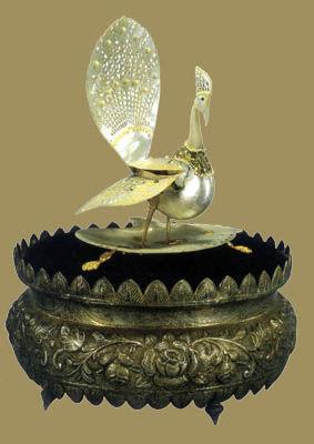 贝雕嵌珍珠孔雀。1966年4月,巴基斯坦达卡市民招待会赠刘少奇。该礼品由孔雀和底座两部分组成。孔雀通体用贝壳精心雕刻,其工艺采用了雕、刻、镂、镶等技法。孔雀双翅张开,彩屏擎起、美目低垂,双腿挺立,形象传神,十分动人。