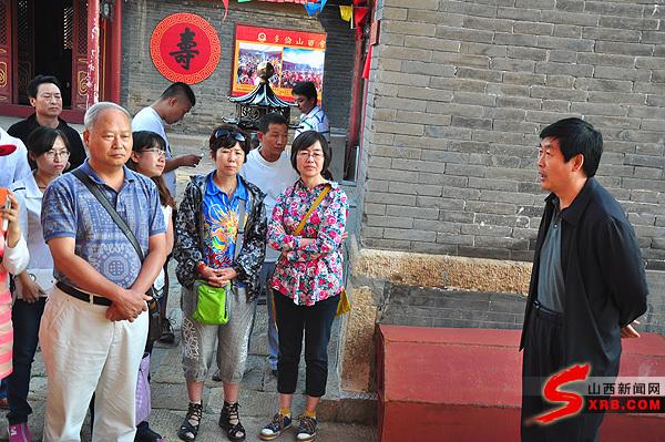钱小虎(右一)向山西文化旅游记者联盟记者讲述修复山西会馆的过程