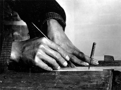"""托好的画心,要用裁板、裁刀、裁尺和锥针之类的工具,打裁纸、绢、绫、锦等装饰材料。接着,用裁好的材料把画心镶嵌起来,这道工序就是""""裱"""",北京话叫""""镶活""""。图中装裱师在裁板上裁绫绢。他先扎出两个洞作为裁切的标记,前一个洞用针锥戳在裁板上,尺靠住针锥使其不移动,后一个洞尺对齐后用手按实。"""